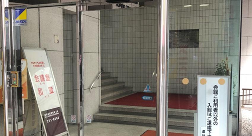 ⑥ここが入り口になります。階段を上って正面のエレベーターの6階で降りてください。右手の突き当りに事務所があります